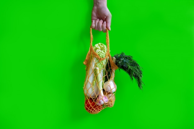 Hand houdt een gebreide tas met groenten: tomaten, knoflook, aardappelen, kool, uien
