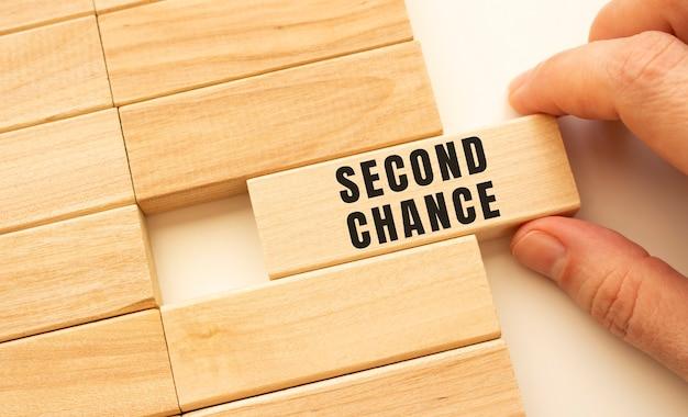 Hand houdt een houten kubus vast met de tekst second chance. positief denken concept