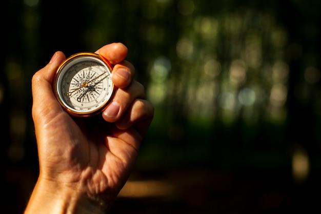 Hand houdt een kompas met onscherpe achtergrond
