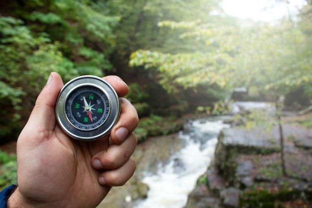 Hand houdt een kompas op de achtergrond van de rivier