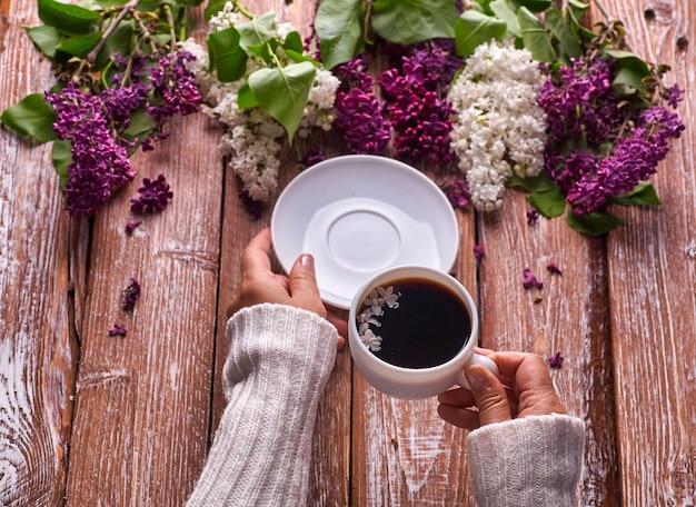 Hand houdt een kopje koffie in de ochtend met lente lila bloemen takken bloeien op houten achtergrond weergave van bovenaf. plat lag ondergrondse stijl. dure kleuren. creatief ontwerp van bloemen.
