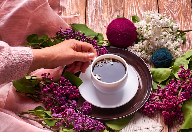 Hand houdt een kopje koffie in de ochtend met lente lila bloemen takken bloeien