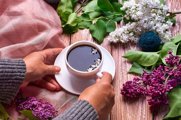Hand houdt een kopje koffie in de ochtend met lila lentebloemen takken bloeien op houten achtergrond weergave van bovenaf.