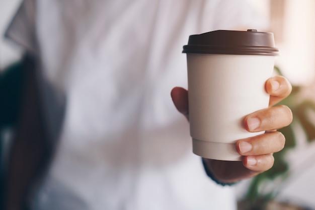 Hand houdt een kopje koffie vast. word 's ochtends wakker met cafeïne-inname.