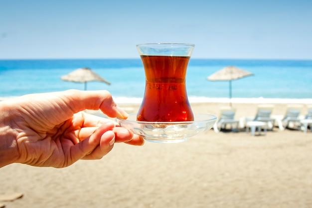 Hand houdt een kopje met traditionele turkse thee.