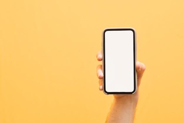 Hand houdt een moderne smartphone vast met een wit, leeg scherm op geel