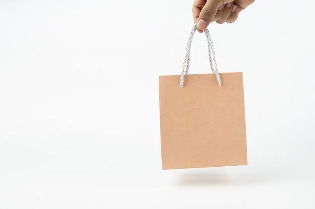Hand houdt een papieren boodschappentas