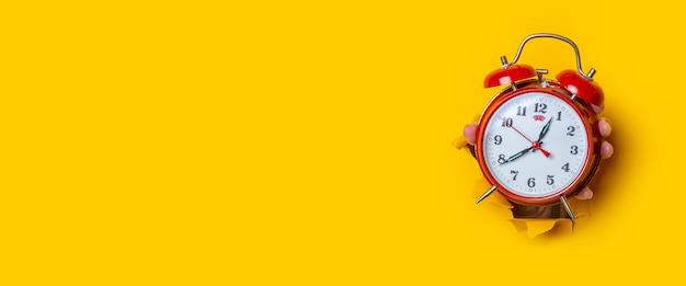 Hand houdt een rood horloge in een gat in een gescheurde gele achtergrond. banier.