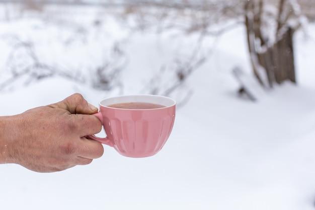 Hand houdt een roze mok met een drankje op een achtergrond van een winterlandschap