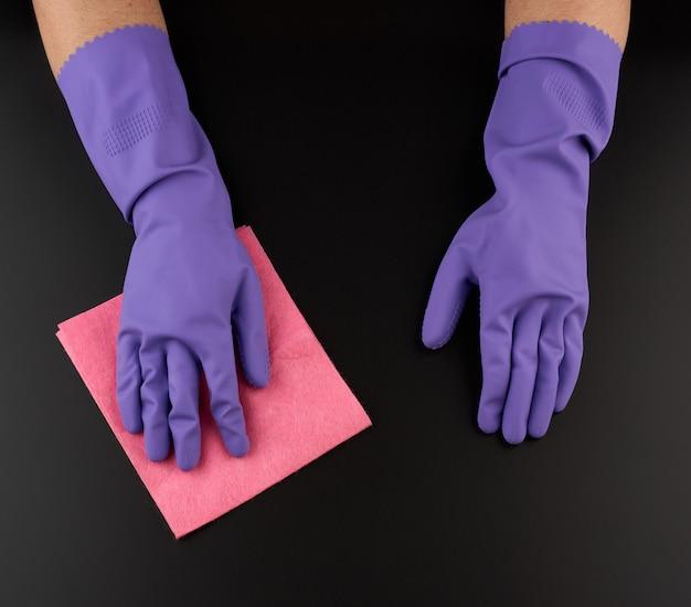 Hand houdt een roze vod spons voor het reinigen, beschermende paarse rubberen handschoen wordt gedragen op de arm