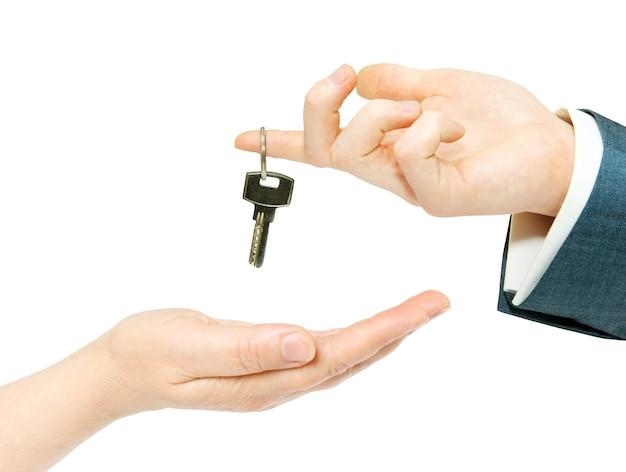 Hand houdt een sleutel op wit wordt geïsoleerd