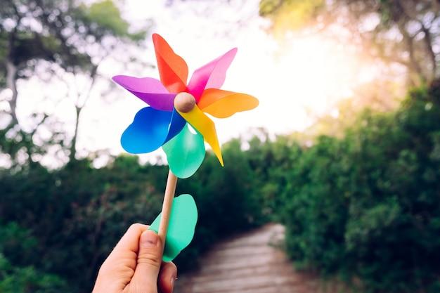 Hand houdt een speelgoed pinwheel, inspiratie en dromen in vrijheid.