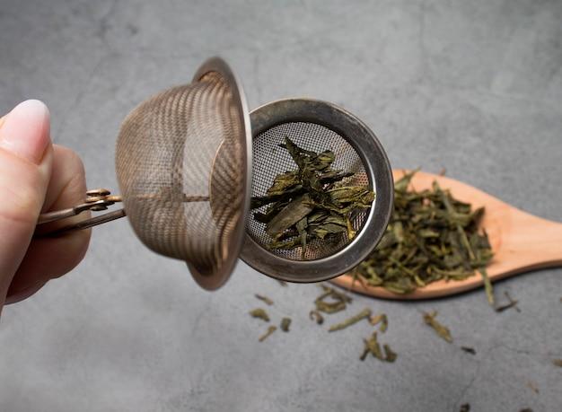 Hand houdt een zeef met groene thee close-up.