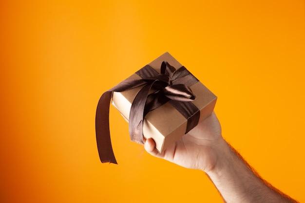 Hand houdt geschenkdoos op oranje achtergrond