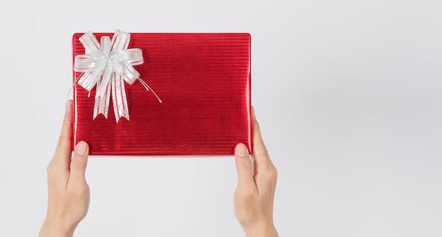 Hand houdt heden of geschenkverpakking vast met rode kleur papier op witte achtergrond.