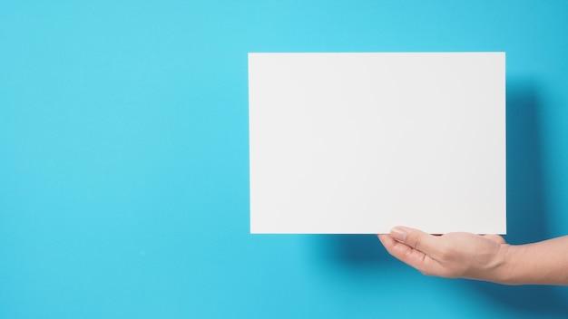 Hand houdt het a4-papier op blauwe achtergrond.