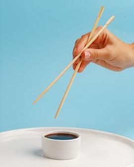 Hand houdt houten stokjes voor sushi. blauw