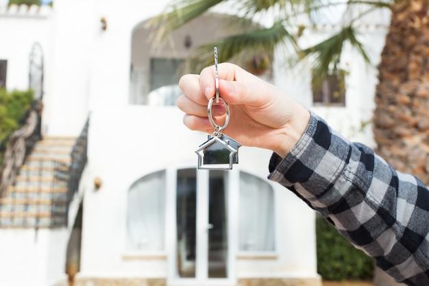 Hand houdt huissleutels op huisvormige sleutelhanger