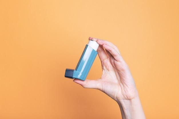 Hand houdt inhalator om astma te behandelen. wereld astma dag. concept van allergiezorg