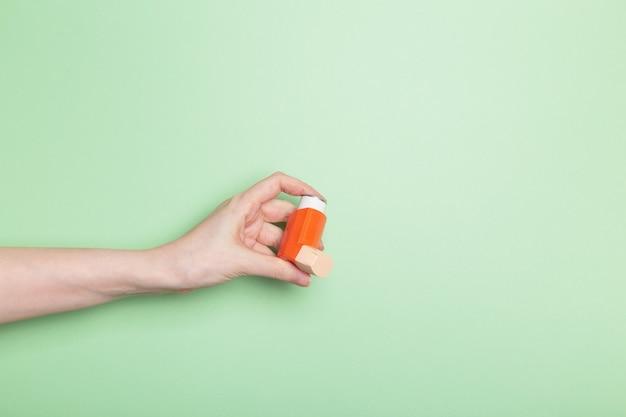 Hand houdt inhalator vast om astma te behandelen. wereld astma dag. concept van allergiezorg. ruimte kopiëren