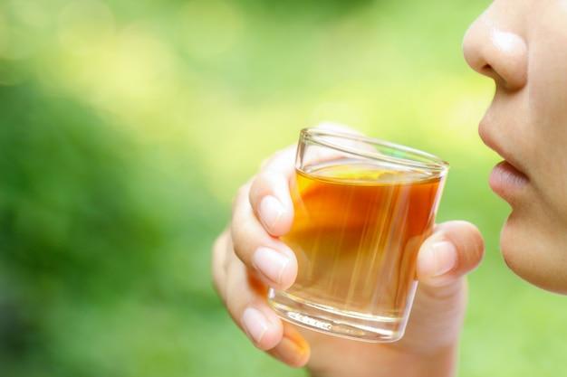 Hand houdt kruidenolie vast voor gezond drinken