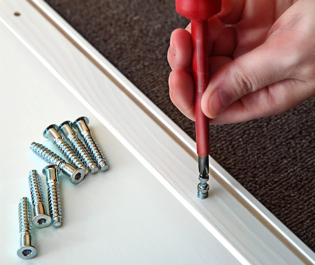 Hand houdt kruisvormige schroevendraaier met rood handvat vast, schroeven hout deuvel is houten paneel, bedekt met witte vlek.