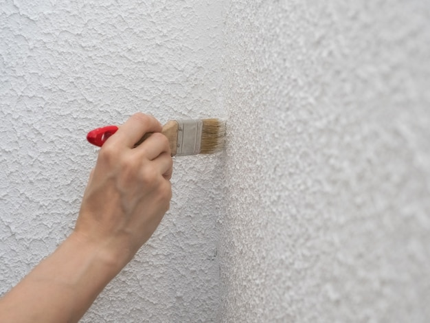 Hand houdt kwast en schilderen van een muur