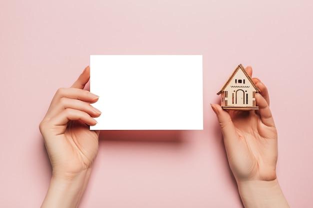 Hand houdt miniatuurmodel van het huis met lege ruimte op een roze ruimte