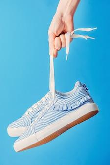 Hand houdt opknoping blauwe sneakers door het veters op een blauwe achtergrond