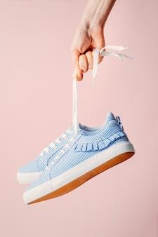 Hand houdt opknoping blauwe sneakers door het veters op roze achtergrond