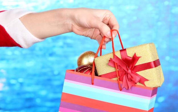 Hand houdt pakket met nieuwjaarsballen en geschenken op blauwe achtergrond