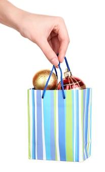 Hand houdt pakket met nieuwjaarsballen op wit wordt geïsoleerd