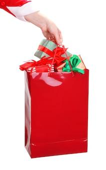 Hand houdt pakket met nieuwjaarsgeschenken op wit wordt geïsoleerd