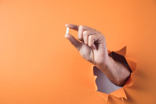 Hand houdt pil op oranje achtergrond