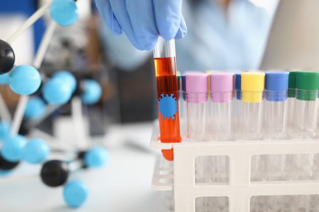 Hand houdt reageerbuis met vloeistof met coronavirus bacteriën