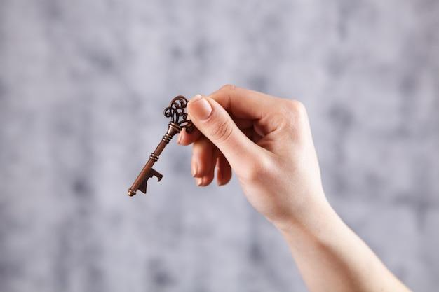 Hand houdt sleutel op grijs