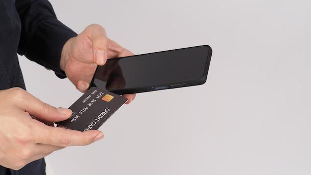 Hand houdt slimme telefoon en zwarte creditcard op witte achtergrond. olympus digitale camera