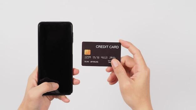 Hand houdt slimme telefoon en zwarte creditcard op witte achtergrond.
