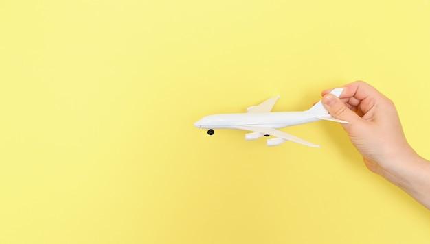 Hand houdt speelgoed vliegtuig op gele achtergrond. zomervakantie concept, reizen. kind plezier op zomervakantie. kopieer ruimte ...