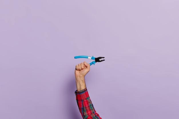 Hand houdt tang met blauwe plastic handvatten voor constructie en reparatie