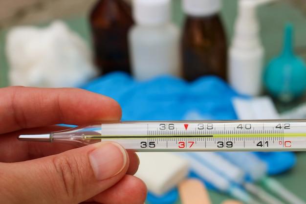 Hand houdt thermometer. lichaamstemperatuur van 38,4 c.