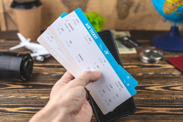 Hand houdt vliegtickets en een telefoon boven een houten tafel met andere reisaccessoires