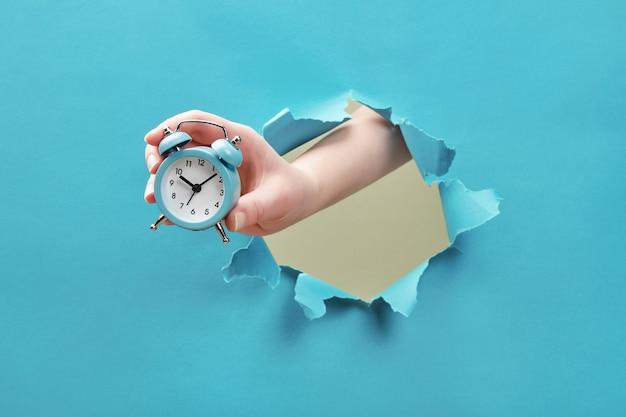 Hand houdt wekker door een papieren gat. tijdbeheer en deadline concept