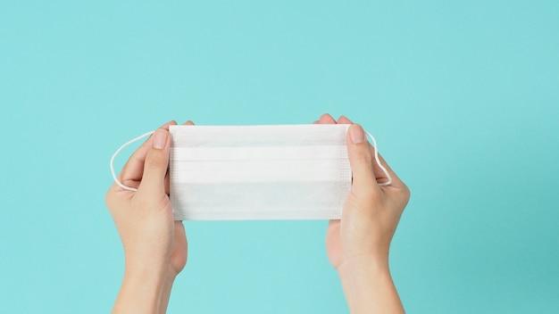 Hand houdt wit chirurgisch gezichtsmasker of wegwerpmasker op mintgroene of tiffany blauwe achtergrond.