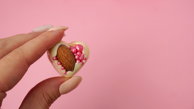 Hand houdt witte chocolade snoepjes met amandelen hartvormige snoepjes