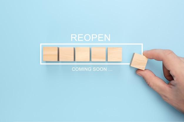 Hand houten kubus op virtuele infographic laadbalk zetten met reopen binnenkort formulering.
