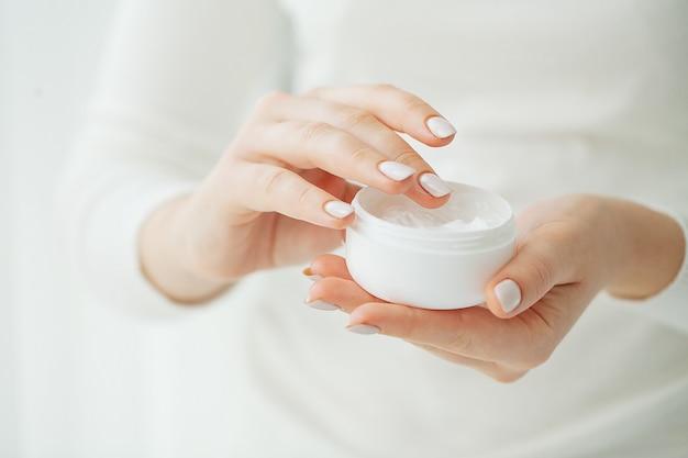 Hand huidverzorging. close-up van vrouwelijke handen met crème buis, mooie vrouw handen met natuurlijke manicure nagels cosmetische handcrème toe te passen op zachte zijdeachtige gezonde huid