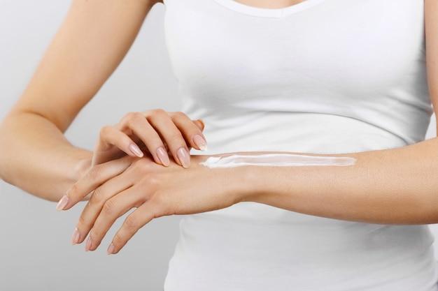 Hand huidverzorging. close-up van vrouwelijke handen room toe te passen