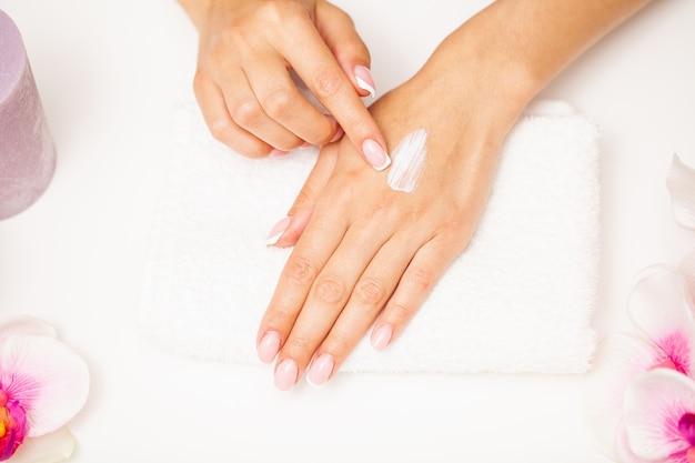 Hand huidverzorging, vrouw brengt vochtinbrengende crème aan op een zachte, zijdezachte huid