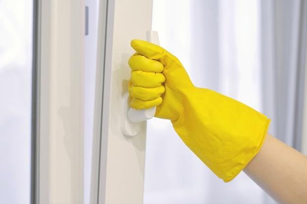 Hand in beschermende gele rubberen handschoen opent en sluit kunststof raam, pvc